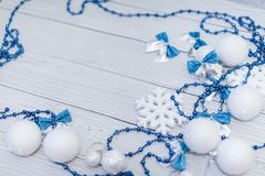 Christmas or newyear frame composition in silver white and blue colors with balls snowflake bows and beads on white wood. Christmas or new year frame composition stock images