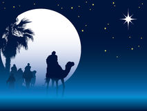 Christmas night. Nativity scene with wise men on camels going through the desert Royalty Free Stock Photo