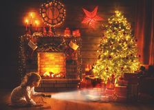 Christmas night. baby girl with a flashlight at night looking for gifts under Christmas tree royalty free stock photography