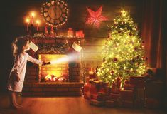 Christmas night. baby girl with a flashlight at night looking fo Royalty Free Stock Photos