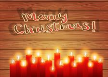 Christmas night. Burning candles on a wooden background. Celebra. Christmas letter. Red burning candles on a wooden background. Christmas background. A postcard Royalty Free Stock Photos