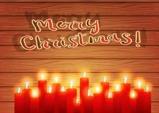 Christmas night. Burning candles on a wooden background.. Christmas letter. Red burning candles on a wooden background. Christmas background. A postcard in a Royalty Free Stock Photo
