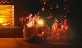 Christmas night. child girl with a flashlight at night looking f Royalty Free Stock Image