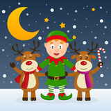 Christmas Night with Elf & Reindeer. Happy cartoon Christmas elf character smiling with two cute reindeer, in a snowy scene with the moon. Eps file available Stock Photos