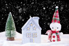 Christmas night idyll with small house toy and snowman and fir tree. New year and Christmas night idyll with small house toy and snowman and fir tree. It`s stock photography