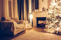 Christmas night in room. Beautiful holdiay decorated room with Christmas treem armchair and fireplace at night. Led lighting, cozy home scene. Nobody there Stock Photos