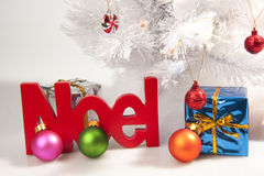 Christmas Noel. A close-up of the word Noel under a white Christmas tree and presents Royalty Free Stock Images