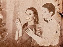 Christmas nostalgy couple on Christmas party 1910-1940. Man and women drink champagne and take gift box near Christmas tree. vintage sepia old photo royalty free stock photos