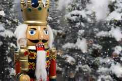 Christmas Nutcracker King. Wearing crown and holding scepter, snow covered evergreen trees blurred in background Stock Photography