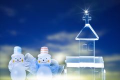 Christmas Objects. Two snowmen by crystal church isolated on dark blue background Royalty Free Stock Photography