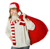 Christmas old man with beard in red hat carrying Santa Claus bag Stock Photography