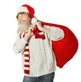 Christmas old man with beard in red hat carrying Santa Claus bag Royalty Free Stock Photography
