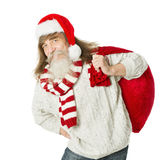 Christmas old man with beard in red hat carrying Santa Claus bag Stock Photos