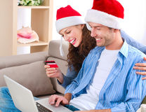Christmas Online Shopping. Young couple with laptop and credit card buying online royalty free stock images