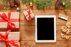 Christmas online shopping background. Tablet screen with copy space top view on wood, credit card and present boxes. Electronic devices, internet commerce on royalty free stock photos