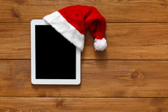 Christmas online shopping background. Tablet screen in santa hat top view on wood with copy space. Electronic devices, internet commerce on winter holidays Royalty Free Stock Photography