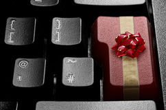 Christmas online shopping concept. Computer enter key wrapped with decorative bow and red ribbon Royalty Free Stock Image