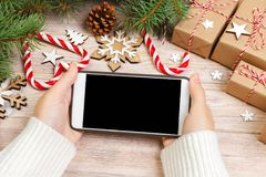Christmas online shopping. Female buyer makes order at screen of smartphone with copy space. Woman buys presents for xmas eve, sit Stock Photography