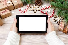 Christmas online shopping. Female buyer touch screen of tablet, copy space. Woman buys presents, among gift boxes on white wood ta Royalty Free Stock Image
