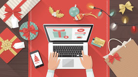Christmas online shopping. Man purchasing Christmas gifts online using a laptop on his desk, shopping bags and decorations all around, holiday and celebrations Stock Image