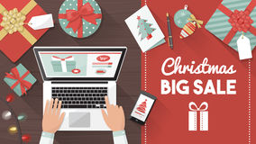 Christmas online shopping. Man purchasing Christmas gifts online using a laptop on his desk, shopping bags and decorations all around, holiday and celebrations Royalty Free Stock Images