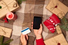 Christmas online shopping with phone. Online shopping concept, gift box. Man buyer makes order at screen of smartphone with copy s