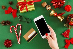 Christmas online shopping background. Christmas online shopping. Smartphone, credit card with copy space on green table with christmas staff. Preparing for Stock Photo