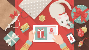 Christmas online shopping. Woman purchasing Christmas gifts online using a tablet, her cat is playing with a bauble on the desk, holiday and celebrations banner Royalty Free Stock Photos