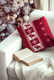 Christmas. Opened book on the cozy chair with warm blanket and cushion on it near Christmas tree Royalty Free Stock Image