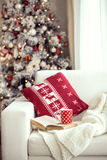 Christmas. Opened book and a cup of tee on the cozy chair with warm blanket and cushion on it near Christmas tree Stock Photography