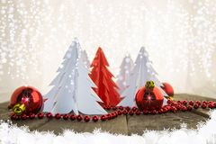 New Year`s decorations, bright red and white. Christmas origami trees on a wooden surface with red beads and red shiny balls Royalty Free Stock Photography