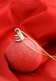 Christmas ornament. On red satin royalty free stock images