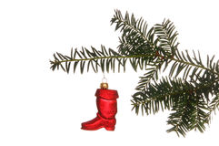 Christmas Ornament. Of a red boot hanging from a pine branch set against a white background Stock Image