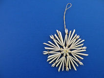 Christmas Ornament. Traditional Christmas straw ornament on dark blue background Stock Photography