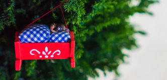 Christmas ornament of a baby in a red cradle hanging on tree Royalty Free Stock Photo