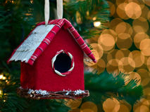 Christmas ornament - bird house. /feeder hanging on a tree with blurred lights in the background stock image