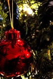Christmas Ornament (Close-Up)1. Red Christmas ornament hanging in a tree. Nice lighting & reflections, Says Merry Christmas in white script Stock Photo