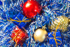 Christmas ornament closeup photo. Red and gold ball. Golden pine. Blue and red wrapped gifts. Royalty Free Stock Images