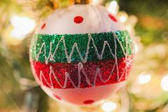 Christmas ornament. Colorful round glittery Christmas ornament hanging from tree with bokeh background royalty free stock photos