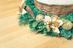 Christmas ornament decorated with a Central in a wicker basket on yellow hardwood floor. royalty free stock photos