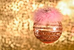 Christmas ornament, decoration, golden ball. Golden background with bokeh. The ball decorated with pink fluffy fur, feather. Glass, transparent, stripes stock photography