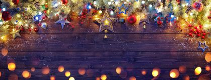 Christmas Ornament With Fir Branches And Lights. On Dark Wooden Plank royalty free stock image