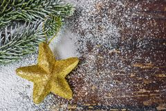 Christmas ornament in the form of star on the board. Golden Christmas ornament in the shape of a heart lying on a fir branch on the wooden board covered with royalty free stock image