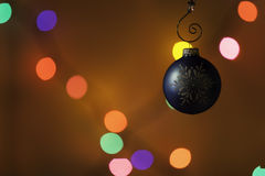 Christmas ornament in front of colorful lights Royalty Free Stock Photography