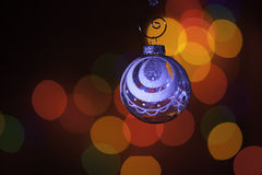 Christmas ornament in front of colorful lights Stock Photos