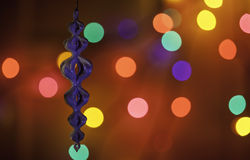 Christmas ornament in front of colorful lights Royalty Free Stock Images