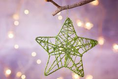 Christmas Ornament Glittering Woven Lace Star Hanging on Tree Branch. Sparkling Garland Lights Pastel Color Background. Greeting Card Poster. Copy Space Stock Photos