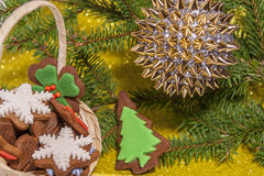 Christmas ornament. With gold bauble and Basket Of Gingerbread Cookies on gold background Stock Photo
