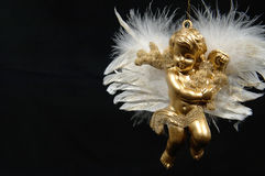 Christmas ornament - Golden Angel, Final part VI. Christmas tree ornament with little golden boy-angel. Wings of feathers, black background. Mostly everything is Royalty Free Stock Images