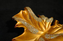 Christmas ornament - Golden Leaf Abstract. Closeup of a golden leaf, Christmas tree decoration on black background Stock Photo